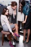 Suchender Berater von den Freunden beim Versuchen auf neuen pinkfarbenen Schuhen Lizenzfreies Stockfoto
