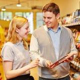 Suchender Rat des Kunden von der Verkäuferin Stockbild