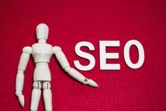 Suchmaschinen-Optimierungs-Konzept SEO, hölzerne Marionette auf rote Farbacryl glaubte Gewebe stockbilder