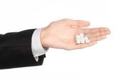 Sucht- und Geschäftsthema: Hand in einem schwarzen Anzug hält Tasche mit weißen Pillen eine Droge auf einem Weiß lokalisierten Hi Lizenzfreies Stockfoto
