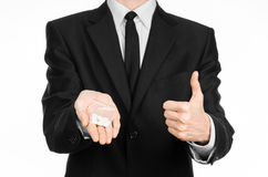 Sucht- und Geschäftsthema: Hand in einem schwarzen Anzug hält Tasche mit weißen Pillen eine Droge auf einem Weiß lokalisierten Hi Stockfotos