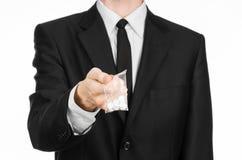 Sucht- und Geschäftsthema: Hand in einem schwarzen Anzug hält Tasche mit weißen Pillen eine Droge auf einem Weiß lokalisierten Hi Lizenzfreie Stockfotos