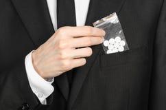 Sucht- und Geschäftsthema: Hand in einem schwarzen Anzug hält Tasche mit weißen Pillen eine Droge auf einem Weiß lokalisierten Hi Stockfoto