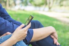 Suchtkonzept des Sozialen Netzes, Paar, das in einer Parkfrau verwendet Handy sitzt Lizenzfreie Stockfotos