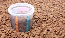 Suchy brown zwierzęcia domowego jedzenie z miarą szkło Obrazy Stock