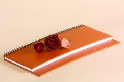 Suchy kwiatu kłamstwo na brown notepad Różany Burgundy i menchie na dzienniczku zdjęcie stock