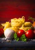 Suchy makaron z warzywami i podprawa na czerwonym drewnianym tle Fotografia Stock