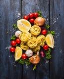 Suchy makaronu tagliatelle z pomidorami, ziele i pikantność dla pomidorowego kumberlandu comosing, Obraz Royalty Free