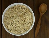 Suchy owsów płatków oatmeal w pucharze na drewnianym stole z drewnianym spoo Fotografia Royalty Free