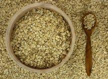 Suchy owsów płatków oatmeal w pucharze na tle z drewnianym spo Obrazy Royalty Free