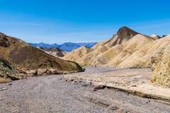 Suchy skalisty riverbed wygina się przez jałowego pustynia krajobrazu kolorowi badlands i szczyty fotografia royalty free