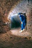 Suchy tunel, mężczyzna pracownik w ochronnym apartamencie w metrze Tajemniczy dungeon tunel Obraz Stock