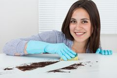 Suciedad de la limpieza de la mano en la tabla con la esponja Fotos de archivo libres de regalías