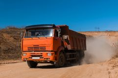Suciedad de mudanza del camión volquete grande en un nuevo proyecto de construcción comercial del desarrollo foto de archivo