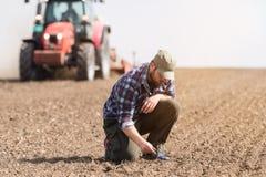 Suciedad examing del granjero joven mientras que el tractor está arando el campo Foto de archivo libre de regalías