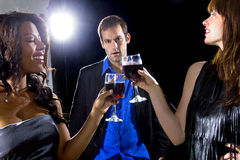 Suckered by Girls at a Nightclub. Women seducing a men to buy them cocktails at a nightclub Royalty Free Stock Photo