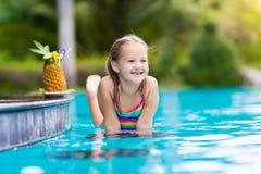 Suco bebendo da criança na barra da piscina Fotos de Stock