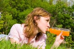 Suco bebendo da mulher no glade do verão foto de stock royalty free