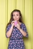 Suco bebendo ou batido da jovem mulher elegante na parede amarela imagem de stock