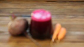 Suco da Beterraba-cenoura no vidro na tabela video estoque
