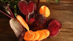 Suco da Beterraba-cenoura no vidro na tabela vídeos de arquivo
