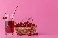 Suco da cereja em um vidro e em um jarro no rosa com bagas maduras dentro fotos de stock royalty free