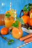 Suco da laranja e de cenoura em uns jarros imagens de stock