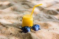 Suco da manga da vitamina em um vidro com os óculos de sol alaranjados de uma palha na areia na costa do mar de turquesa nos tróp Imagem de Stock