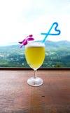 Suco de abacaxi na palha de vidro e azul da forma do coração Imagens de Stock Royalty Free