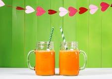 Suco de cenoura em uns frascos de pedreiro imagens de stock