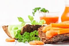Suco de cenoura em vidros bonitos, na cenoura cortada e no aipo na bacia de madeira da casca e na salsa verde no fundo de madeira Imagens de Stock Royalty Free