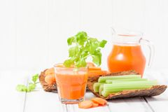 Suco de cenoura em vidros bonitos, na cenoura cortada e no aipo verde na bacia de madeira da casca no fundo de madeira branco Beb Fotografia de Stock Royalty Free