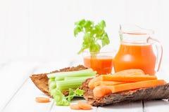 Suco de cenoura em vidros bonitos, na cenoura cortada e no aipo verde na bacia de madeira da casca no fundo de madeira branco Beb Foto de Stock