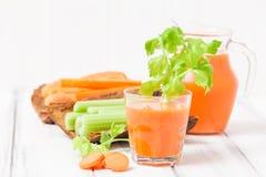 Suco de cenoura em vidros bonitos, na cenoura cortada e no aipo verde na bacia de madeira da casca no fundo de madeira branco Beb Fotos de Stock