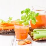 Suco de cenoura em vidros bonitos, na cenoura cortada e no aipo verde na bacia de madeira da casca no fundo de madeira branco Beb Imagem de Stock Royalty Free