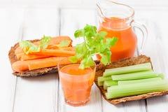 Suco de cenoura em vidros bonitos, na cenoura cortada e no aipo verde na bacia de madeira da casca no fundo de madeira branco Beb Fotografia de Stock