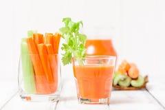 Suco de cenoura em vidros bonitos, na cenoura cortada e no aipo verde na bacia de madeira da casca no fundo de madeira branco Beb Imagem de Stock