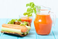 Suco de cenoura em vidros bonitos, na cenoura cortada e no aipo verde na bacia de madeira da casca no fundo de madeira branco Beb Foto de Stock Royalty Free