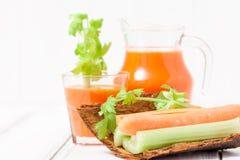 Suco de cenoura em vidros bonitos, na cenoura cortada e no aipo verde na bacia de madeira da casca no fundo de madeira branco Beb Imagens de Stock