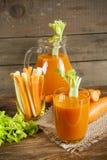 Suco de cenoura fresco com cenouras, aipo, aneto e salsa Imagem de Stock Royalty Free