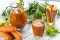 Suco de cenoura fresco com cenouras, aipo, aneto e salsa Fotos de Stock
