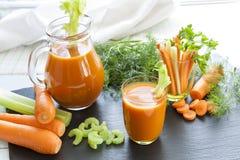 Suco de cenoura fresco com cenouras, aipo, aneto e salsa Imagens de Stock Royalty Free