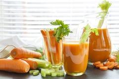 Suco de cenoura fresco com cenouras, aipo, aneto e salsa Imagem de Stock