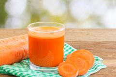 Suco de cenoura fresco no vidro e no vegetal cortado da cenoura no guardanapo na tabela de madeira, borrão, defocused, fundo da n Foto de Stock