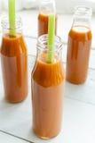 Suco de cenoura natural e fresco em umas garrafas pequenas com aipo fresco Fotos de Stock