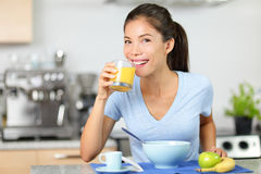 Suco de laranja bebendo da mulher que come o café da manhã Foto de Stock