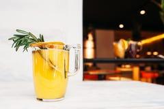Suco de laranja com alecrins no fundo do café Fotos de Stock Royalty Free