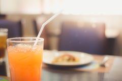 Suco de laranja com o café da manhã do borrão no fundo do restaurante Fotografia de Stock