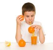 Suco de laranja da bebida do menino com uma palha Imagens de Stock