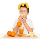 Suco de laranja da bebida do menino com uma palha Imagem de Stock
